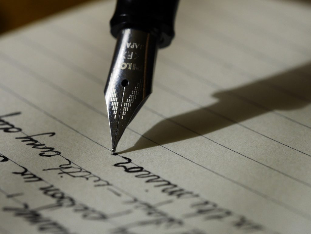 A pen writing on a page