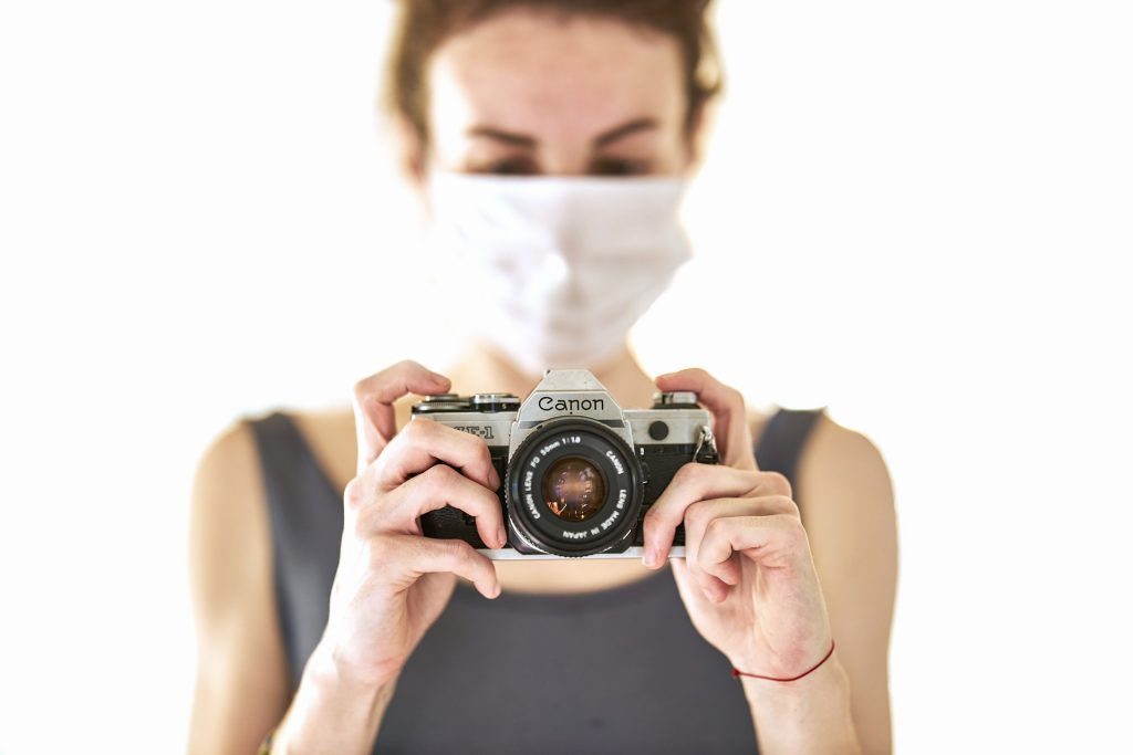 Woman in mask taking photographs