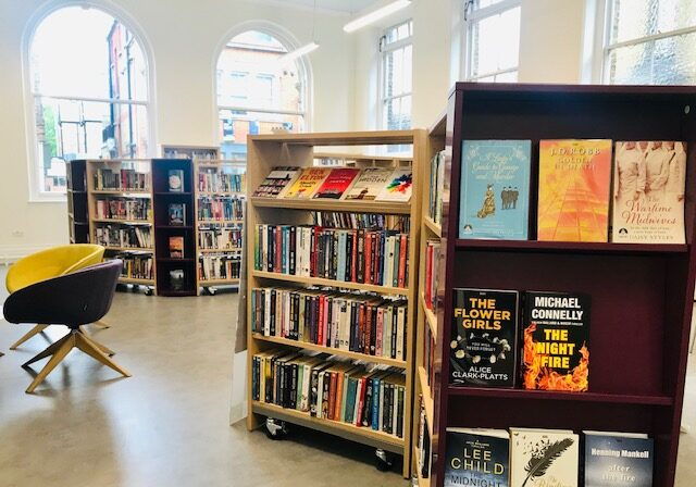 Image of the inside of Twickenham Library, showing multiple shelves of adult fiction books including a display, and two brightly coloured chairs. The background features several large windows letting in plenty of sunlight.