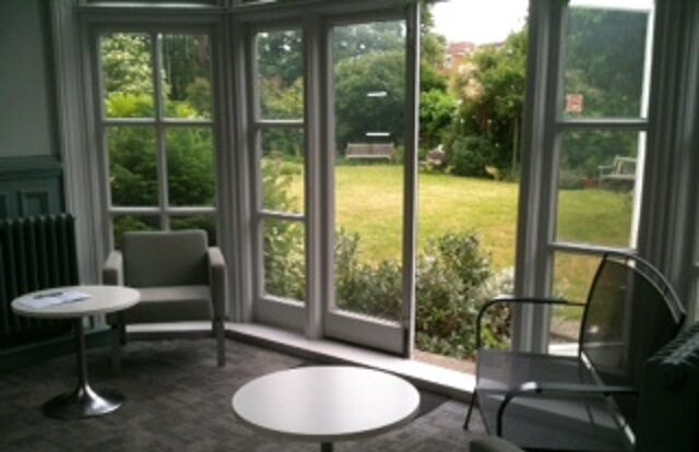 A photo taking inside Teddington Library looking out the windows into the garden. Comfy chairs and small tables can be seen in front of the glass door leading outside.