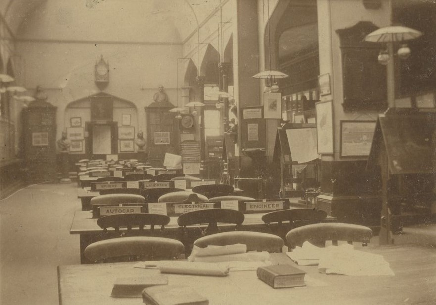 An old photograph of the interior of Richmond Library. Arches run along the right hand side, behind which storage units can just be seen and between the arches are large wooden book rests, some displaying open books. The centre of the library is clear, with a row of desks and chairs running down the centre 3 abreast. On the back wall there is a clock, and two closed cases stand on each side of the wall, each topped with a carved stone bust. 2 more busts rest on their own plinths between the bookcases.
