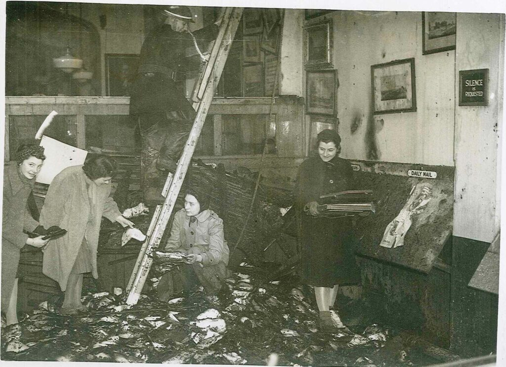 """Second image of the inside of Richmond Library after the bombing. The floor is covered in detritus, and scorch marks can be seen on the walls. One woman carries a pile of newspapers and 3 more are bent over the floor, picking books out of the wreckage. Above them a fireman is climbing a ladder. A sign on the damaged wall reads """"Silence is Requested."""""""