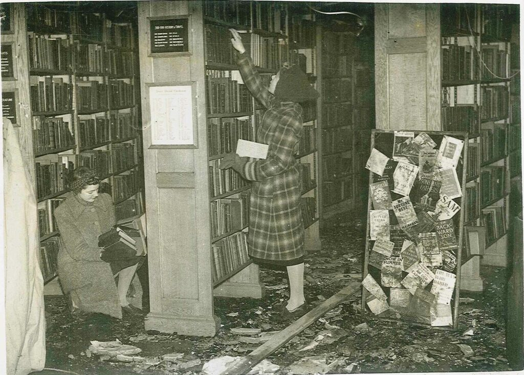 Image showing the clean up effort in Richmond Library after the bombing. Two women are in between the bookshelves, one standing and one sitting, both carrying books in their arms. The sitting woman inspects her books for damage, while the standing woman reaches towards the shelves to retrieve more. Surrounding them on the floor are shards of wood and broken glass. To their right a bulletin board covered in posters leans against a bookshelf, clearly marked, either with charring from the fire or dirt.