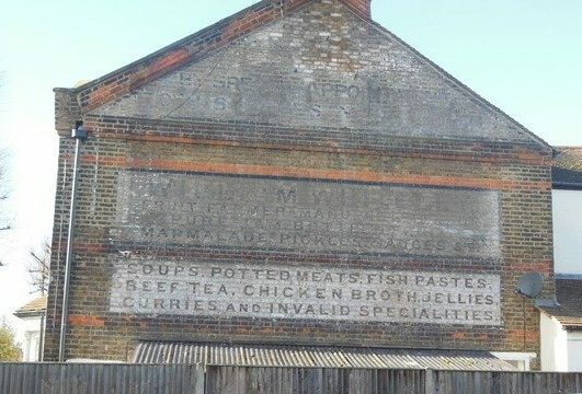 Photo of a brick wall on the end of a house, bearing text advertising William Whiteley's services